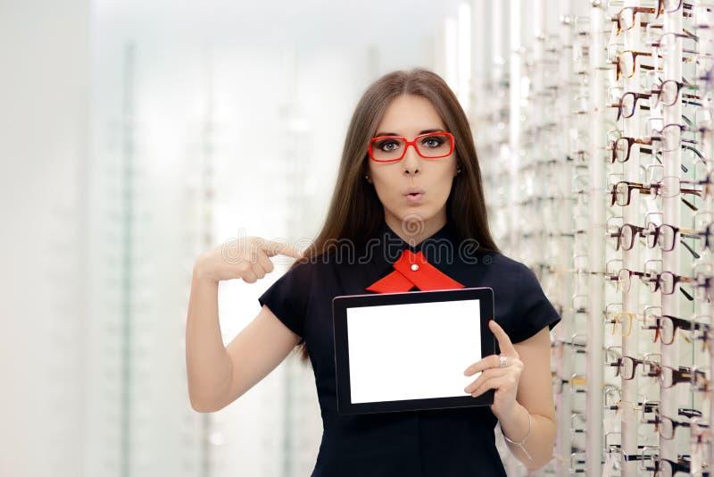 Femme étonnée avec la Tablette de PC dans le magasin optique médical images stock