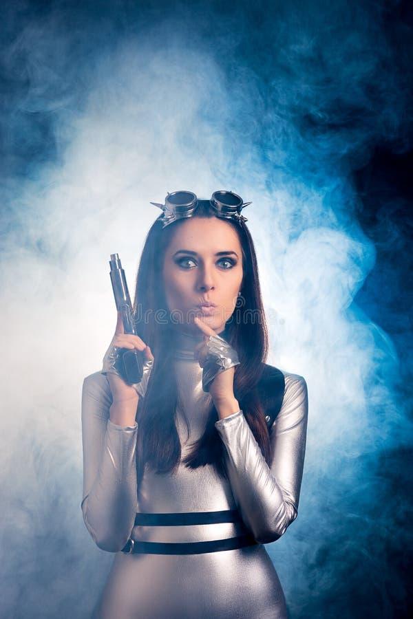Femme étonnée dans le costume argenté de l'espace tenant l'arme à feu de pistolet images libres de droits