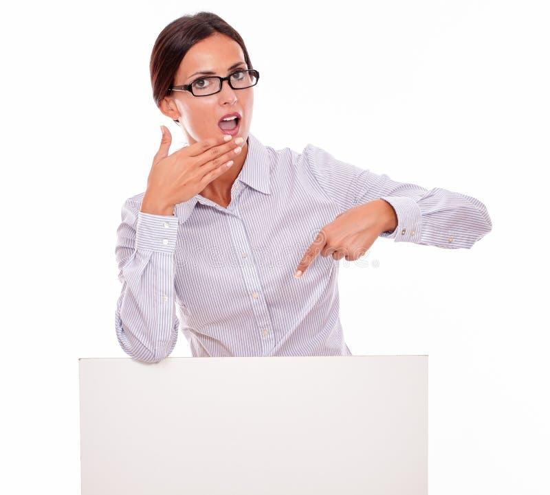 Femme étonnée de brune avec la plaquette vide photographie stock