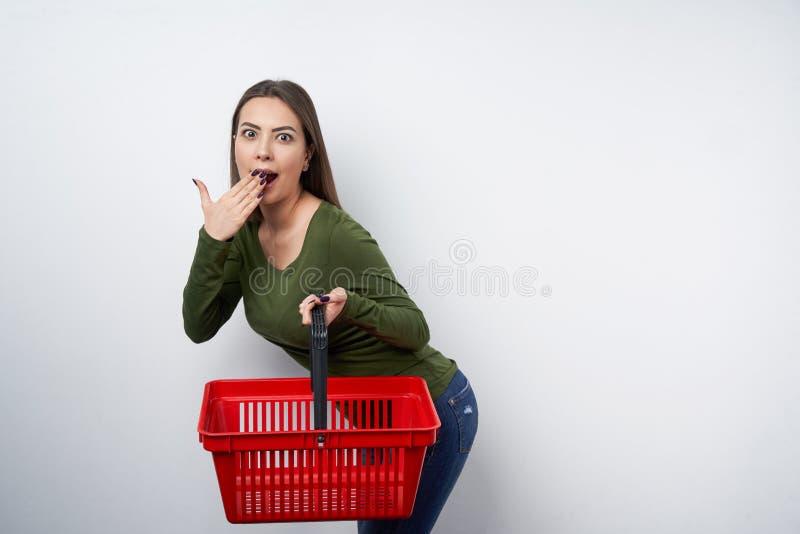 Femme étonnée de brune tenant le panier à provisions vide photos stock