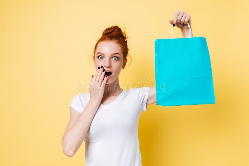 Femme étonnée de gingembre jugeant le paquet disponible et couvrant la bouche images stock