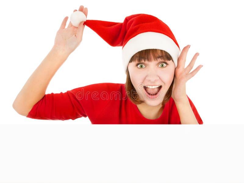 Femme étonnée de Santa jetant un coup d'oeil du panneau-réclame blanc photographie stock libre de droits