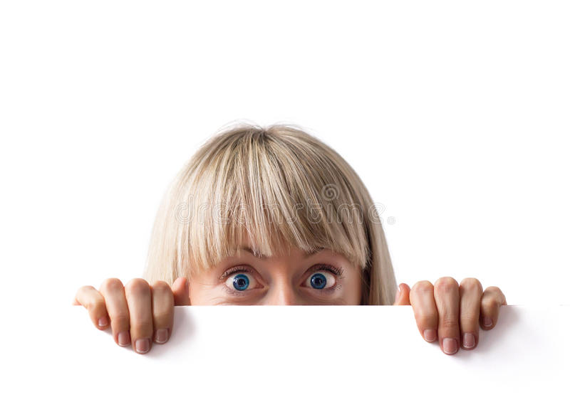Femme étonnée derrière le conseil blanc photographie stock