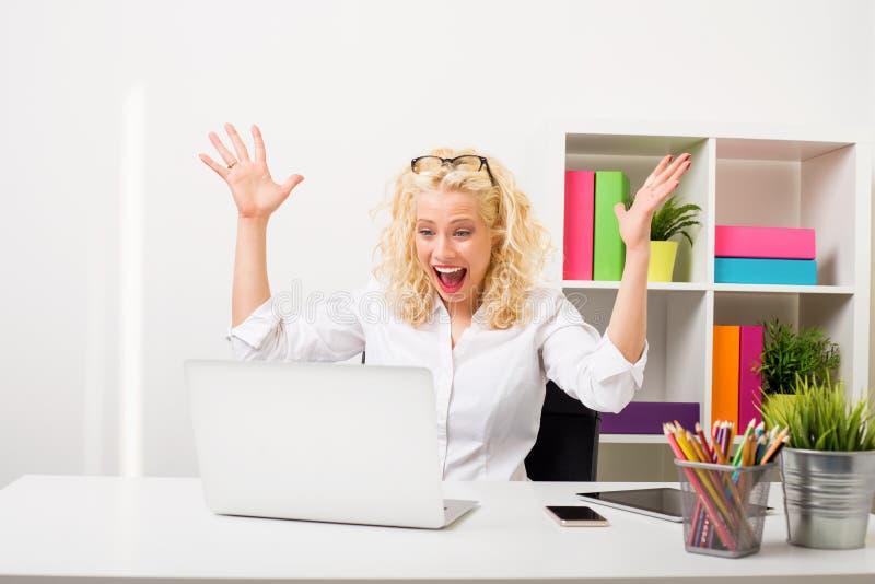 Femme étonnée et heureuse au bureau montrant son excitation image libre de droits