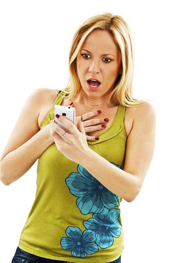 Femme étonnée lisant le message textuel choquant de sms photographie stock