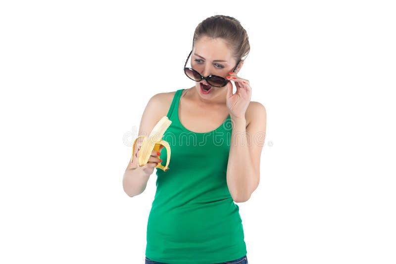 Femme étonnée par photo avec la banane et les lunettes de soleil photos libres de droits