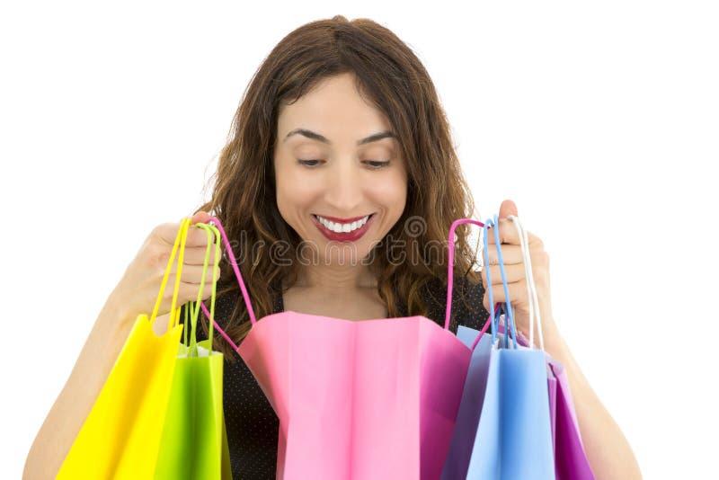 Femme étonnée regardant à son cadeau dans un sac de papier photos libres de droits