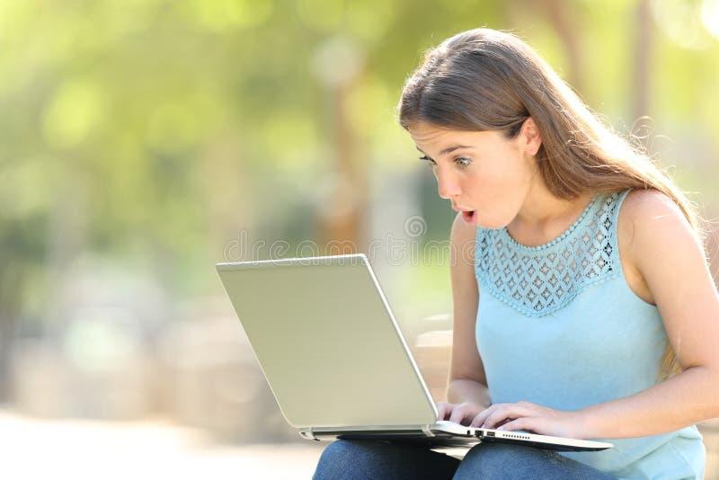 Femme étonnée vérifiant le contenu en ligne d'ordinateur portable photographie stock libre de droits