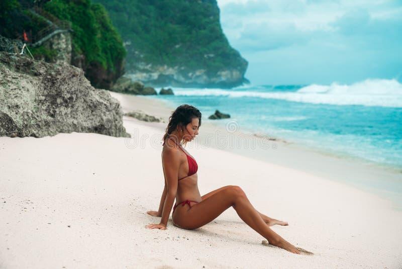 Femme étonnante appréciant le soleil et les vagues sur une plage blanche La brune se met à genoux dans l'eau dans un maillot de b photos libres de droits