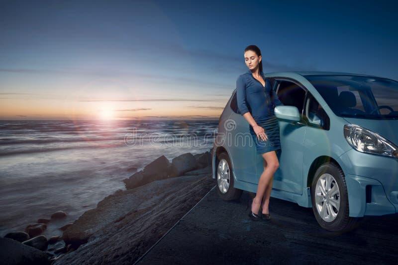 Femme étonnante de beauté posant à côté de sa voiture par la mer au coucher du soleil images stock