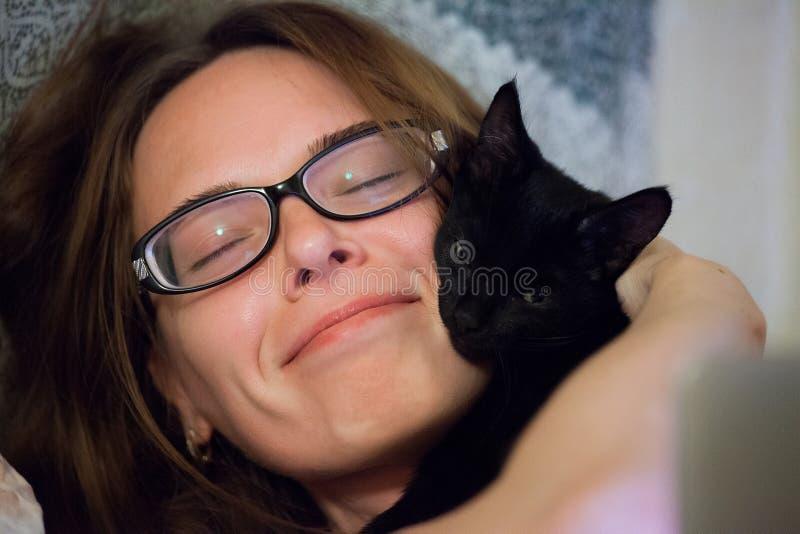 Femme étreignant le chaton noir d'animal familier image stock