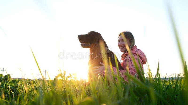 Femme étreignant le chien au coucher du soleil et riant, jeune la fille avec l'animal familier se reposant sur l'herbe et se repo photographie stock