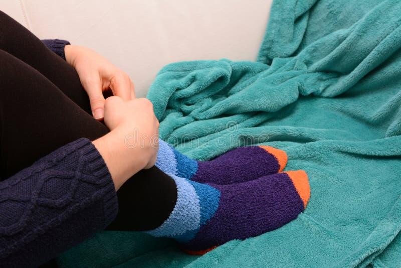 Femme étreignant ses jambes, chaussettes chaudes de port photos stock