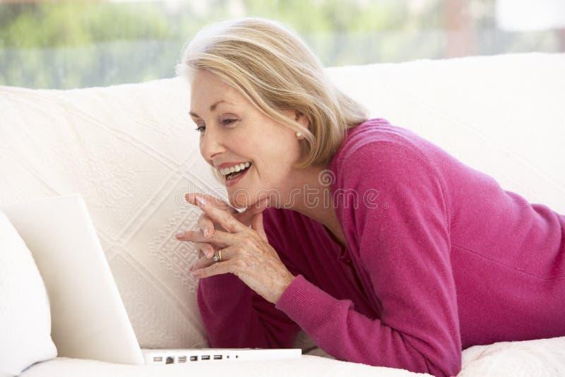 Femme aîné à l'aide de l'ordinateur portatif à la maison images stock