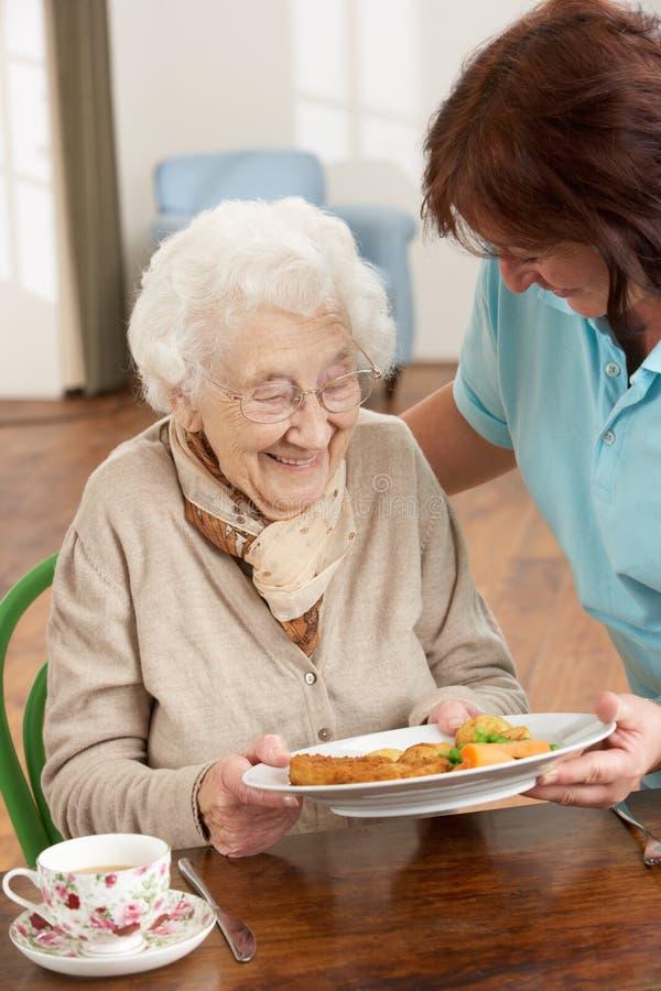 Femme aîné étant servi le repas images libres de droits