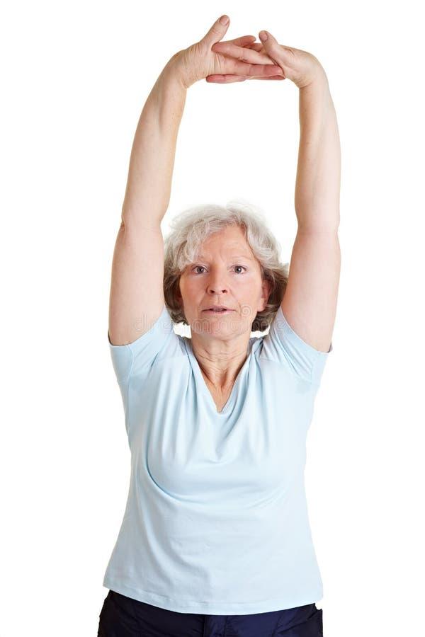 Femme aîné étirant ses bras photographie stock
