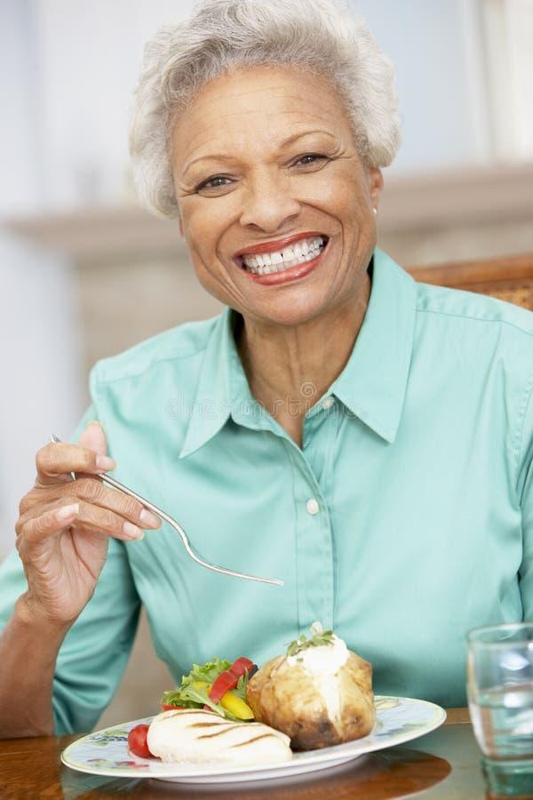 Femme aîné appréciant un repas à la maison images stock