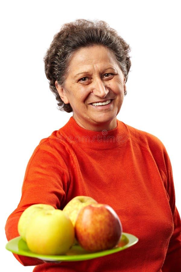 Femme aîné avec des pommes photos stock