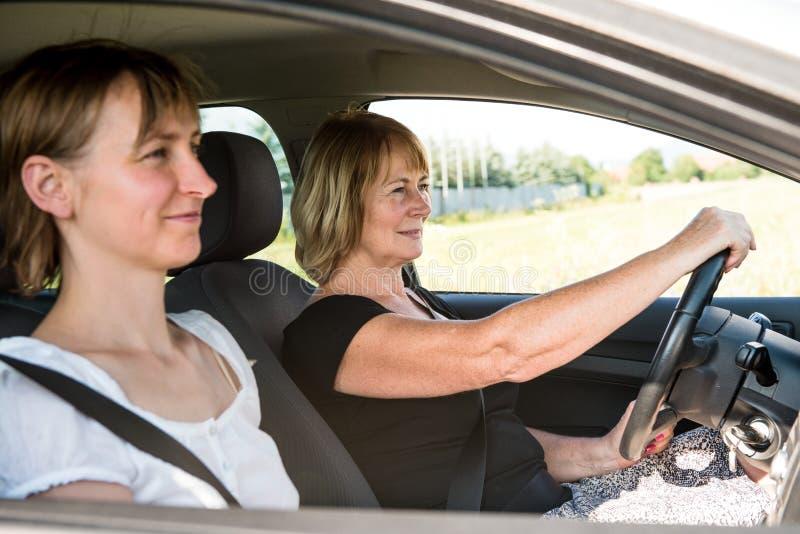 Femme aîné avec le descendant conduisant le véhicule photo stock