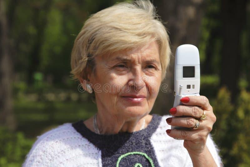 Femme aîné avec le téléphone photographie stock