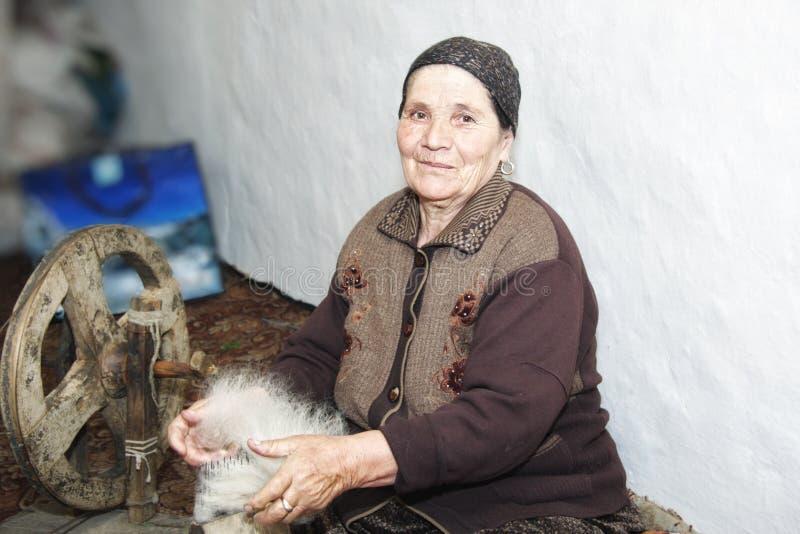 Femme aîné cardant le filé de laine photographie stock