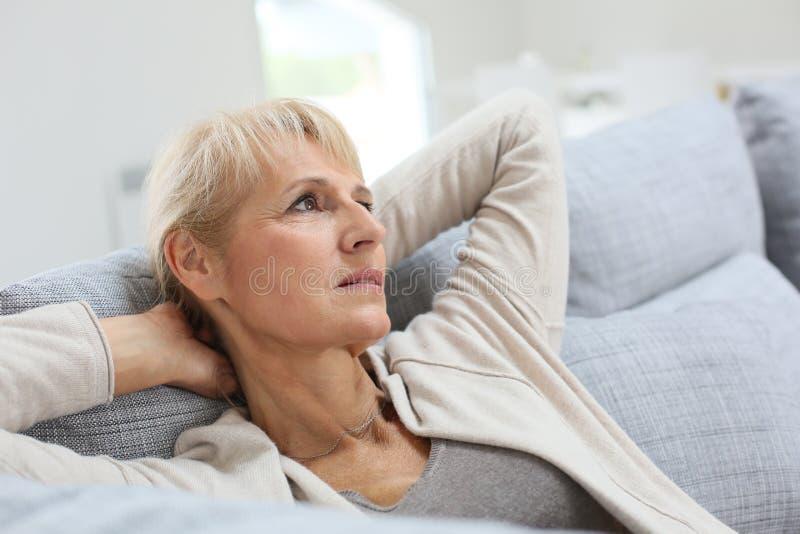 Femme aîné détendant sur le sofa photos libres de droits