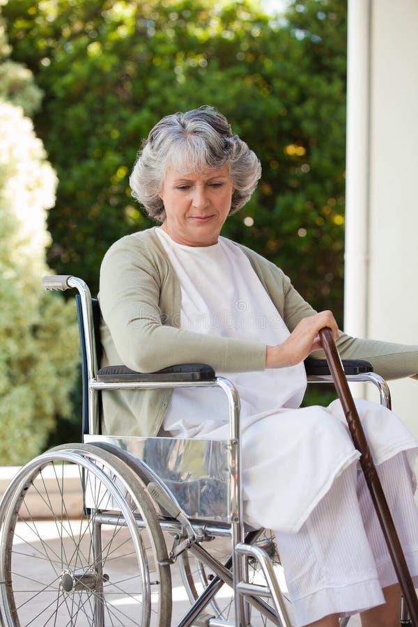 Femme aîné dans son fauteuil roulant image stock