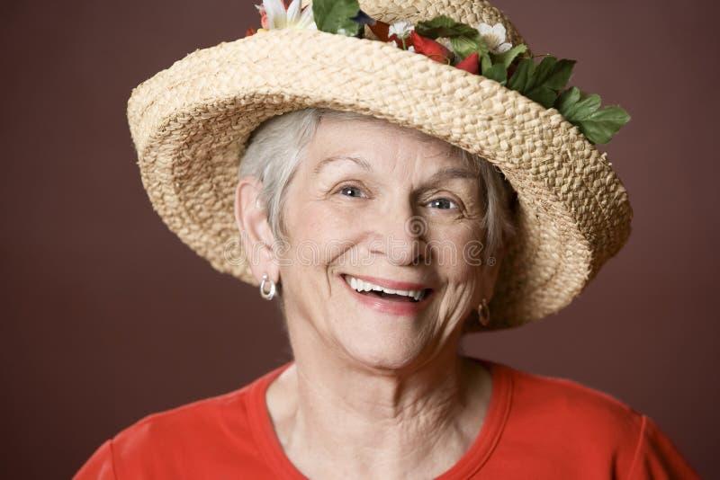 Femme aîné dans un chapeau de paille photo stock