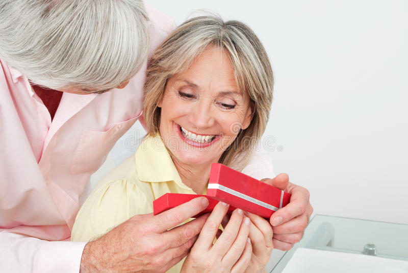 Femme aîné de sourire recevant le cadeau photographie stock