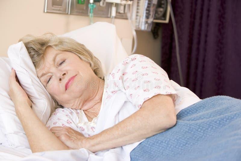 Femme aîné dormant dans le bâti d'hôpital photos libres de droits