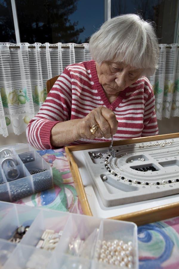 Femme aîné effectuant un collier photos stock