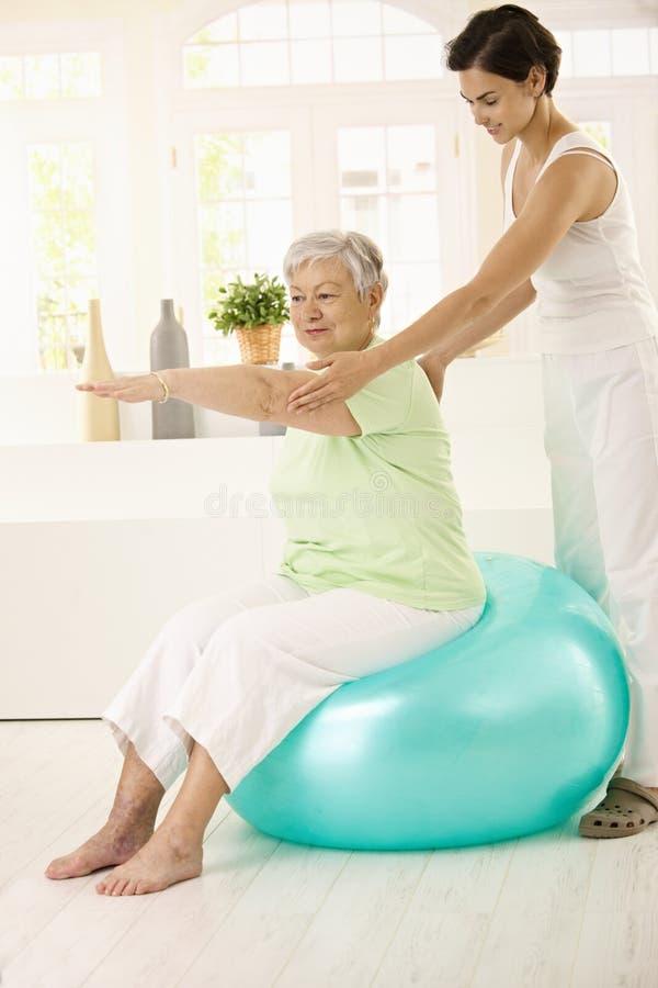 Femme aîné faisant l'exercice convenable de bille images stock