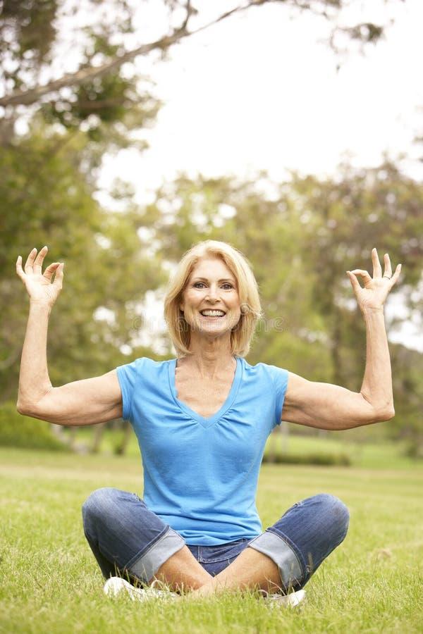 Femme aîné faisant le yoga en stationnement photos libres de droits