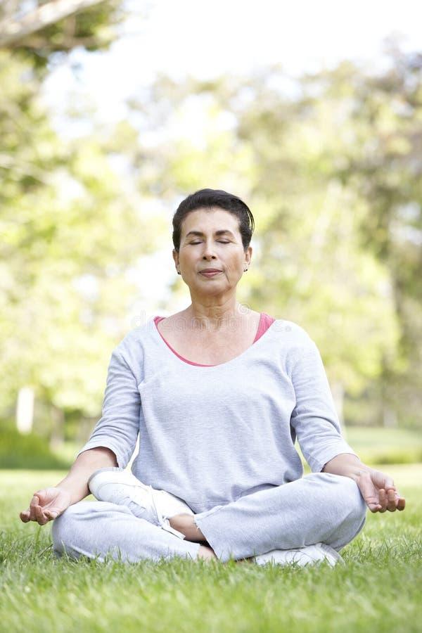 Femme aîné faisant le yoga en stationnement image libre de droits