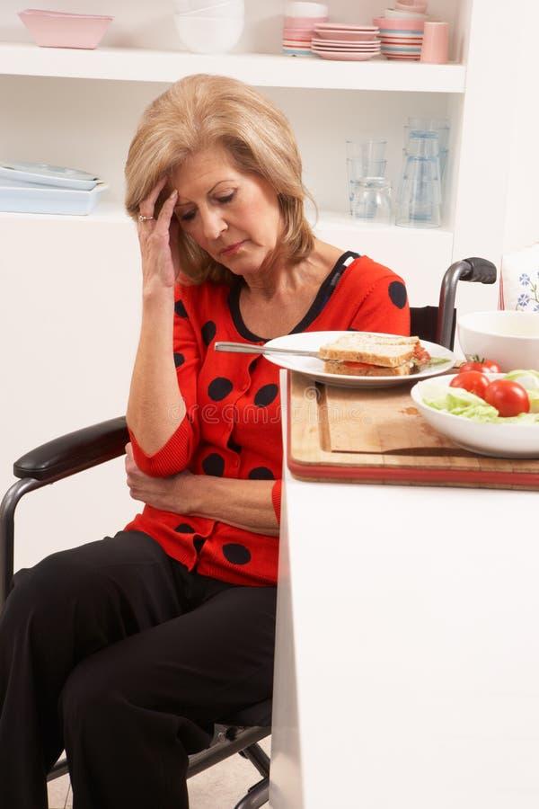 Femme aîné handicapé affligé effectuant le sandwich photo stock