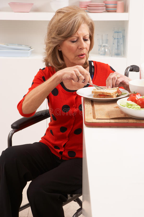 Femme aîné handicapé effectuant le sandwich photo libre de droits