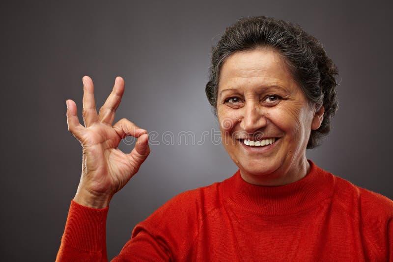Femme aîné heureux effectuant le signe en bon état images stock