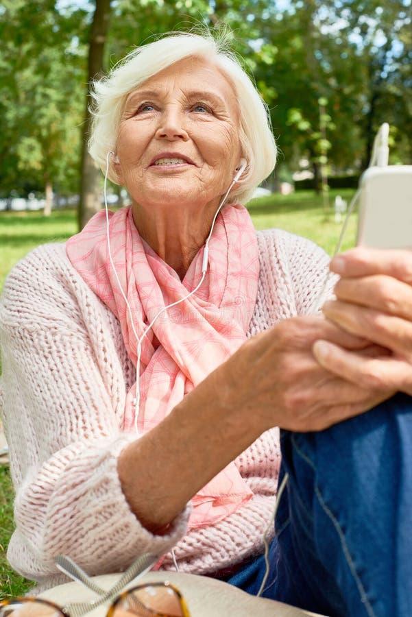 Femme aîné heureux utilisant le smartphone photos stock