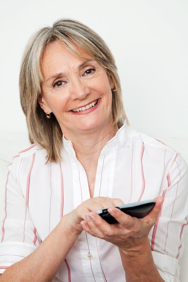 Femme aîné heureux utilisant le smartphone image stock