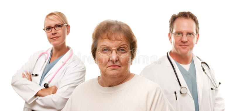 Femme aîné intéressé avec médecins Behind photos stock