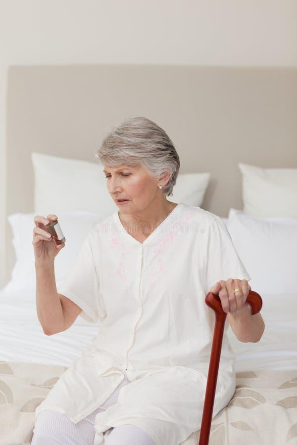 Femme aîné malade prenant ses pillules image libre de droits