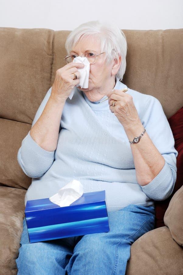 Femme aîné malade soufflant son nez image stock
