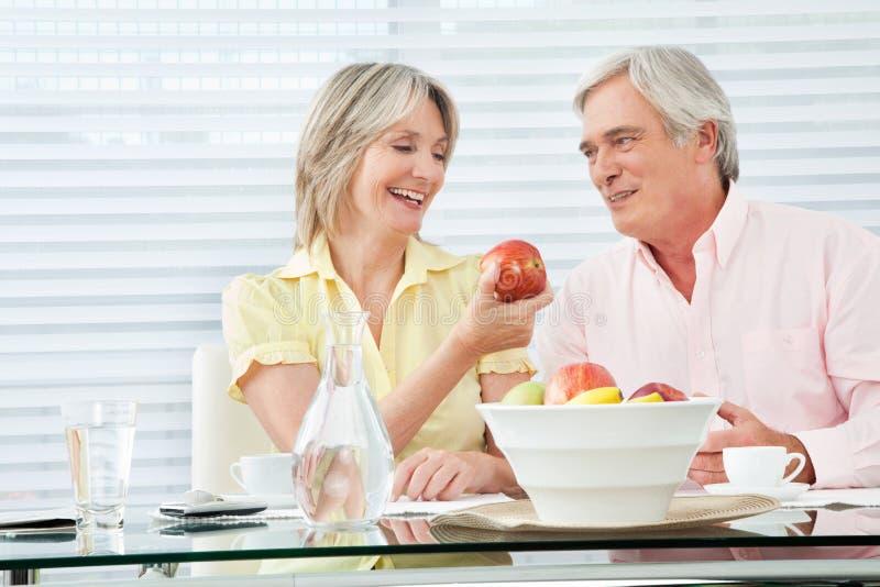 Femme aîné offrant la pomme rouge photos stock