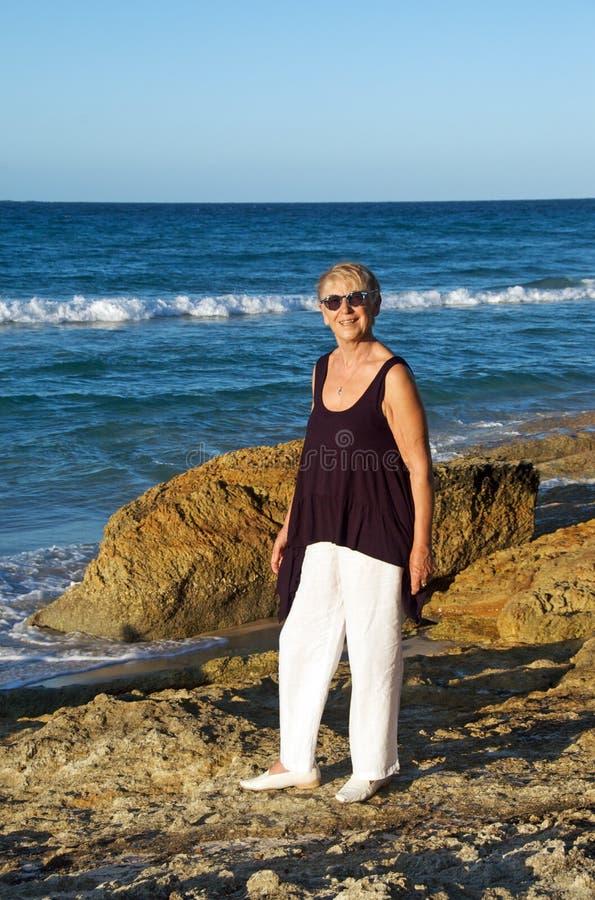 Femme aîné par la mer image libre de droits