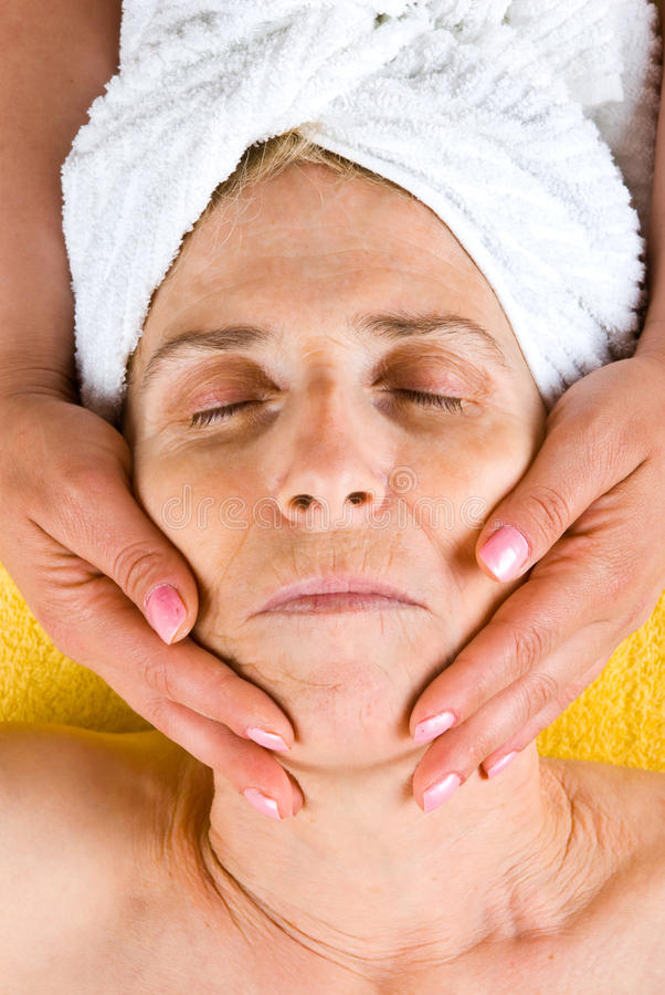 Femme aîné recevant un massage facial photos stock