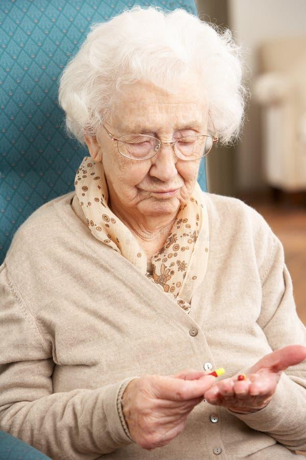 Femme aîné regardant le médicament photographie stock libre de droits