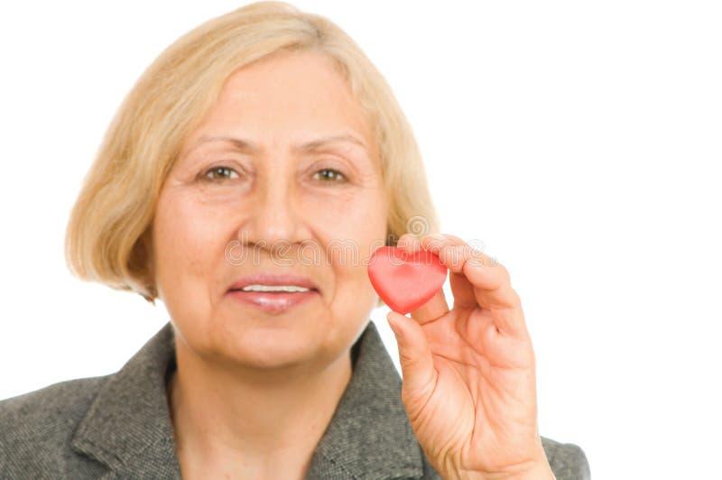 Femme aîné retenant le coeur rouge images stock