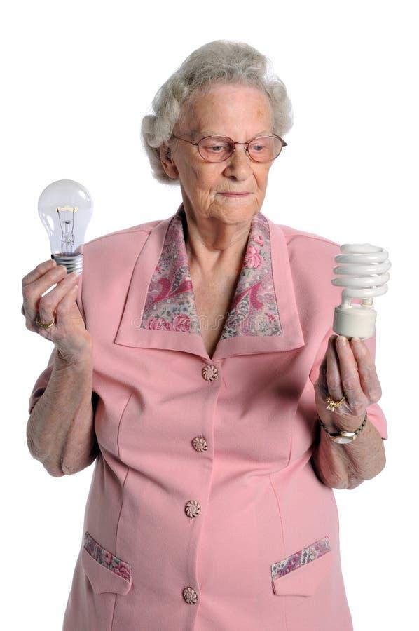 Femme aîné retenant les ampoules images stock