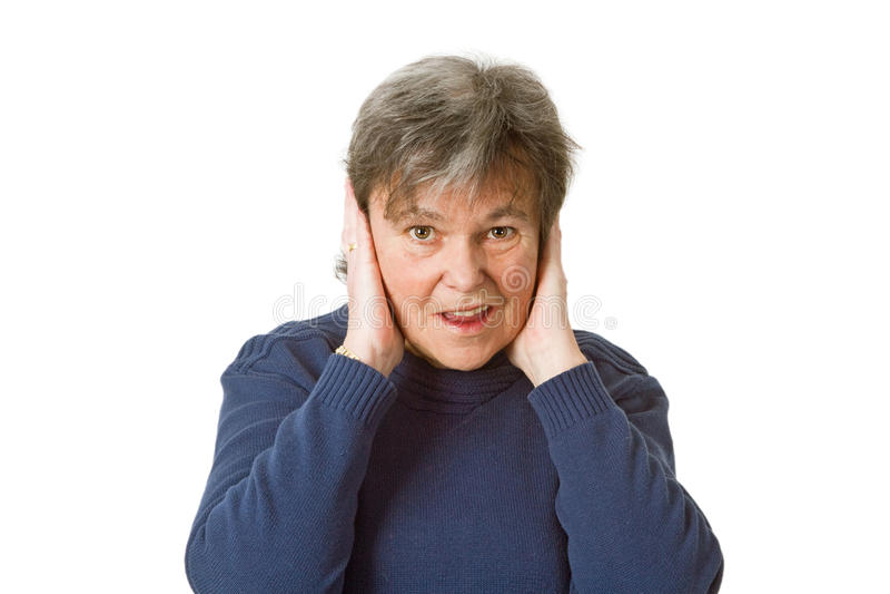 Femme aîné retenant ses oreilles photo stock