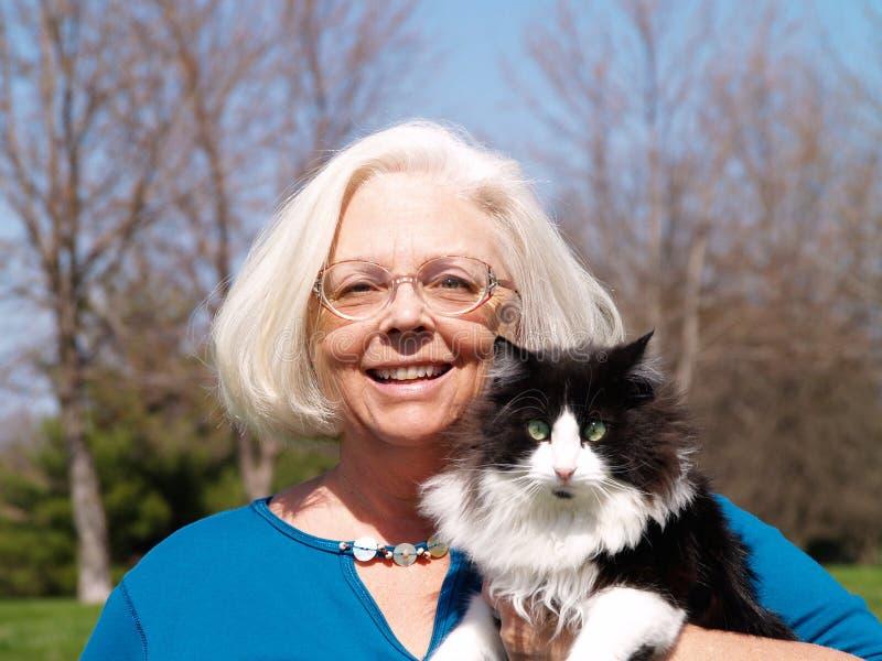 Femme aîné retenant un chat image stock